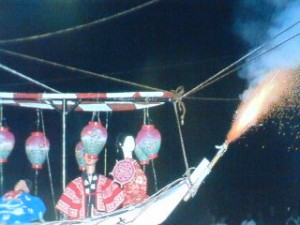 Fire shoots out of a small, puppet-bearing boat during Tsunabi