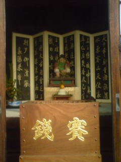 An offerings box reading- SAISEN ( offerings) in front of an image of EBISU, one of the Seven Deities of Good Fortune