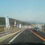 Exiting the Asahi Tunnel on the Yasato Side - the road is lined with banners advertizing various orchards which offer fruit picking
