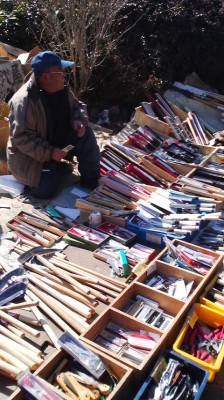 A man displays his knoves and bladed tools
