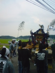 A typical Gion Matsuri Festival- A portable shrine (Omikoshi) being carried and shaken to absorb all impurities in the village- bamboo poles have been set to mark the village boundary