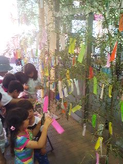 Children writing out their wishes to hang on the Tanabata decoration in front of a supermarket in Matsushiro, Tsukuba