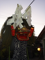 A closer look at the SHISHI`s wooden head- called a SHISHIGASHIRA (note the lightning shaped white strips of paper (GOHEI) which are meant to keep impurities away and also act as an attractant for a deity or spirit)