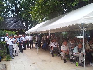 In the stifling humidity, DANKA (people whose families have their graves at the temple) wait for the ceremony to begin