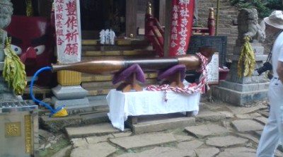 Japan`s largest Kiseru ( traditional pipe) is filled with tobacco, lit, and while smoking carried up Mt Kaba to the Tobacco Shrine- notice the pump inserted into the mouth-piece which helps keep the tobacco lit!