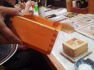 One large MASU, made of untreated cypress wood, is used to pour SAKE into a smaller one till it overflows
