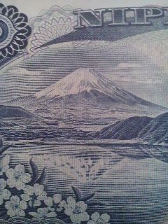 On the back side of the one-thousand Yen bill is this view of Mt. Fuji as seen behind Lake Motosu (本栖湖) and cherry blossoms in bloom. The engraving is based on a  1935 photo taken by the photographer Okada Koyo (岡田紅陽).