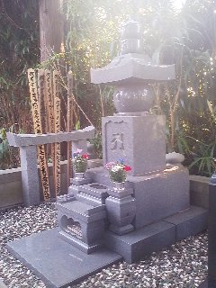 The grave of a former head priest of the Henjo-In Temple in Teshirogi, Tsukuba- with offerings of flowers and incense for O-Higan (Febuary 23, 2014)- the grand tombstone takes the form of GORIN TO monument symbolizing earth,water,fire,wind and sky. Note the Shinto Torii gate and the SOTOBA wooden memorial slabs engraved in Sanskrit and Kanji, a reminder of the days before the Meiji Restoration, before Shintoism and Buddhism had been separated