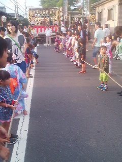 Children pulling a float (DASHI) along. On the float are the festival musicians and dancers.
