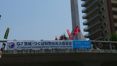 The May Day Parade proceeds over the Sakura Bridge between and Nova Hall and Capio - and past the banner announcing this year`s (2016) G-7 Summit in Tsukuba (the meeting for science and technology ministers)